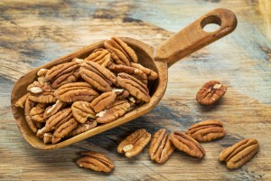 pecan nuts in a rustic scoop against a grunge wood background