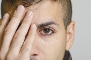 Young man coverin eye
