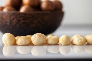 Bowl of Macadamia nuts, with shelled nuts in foreground