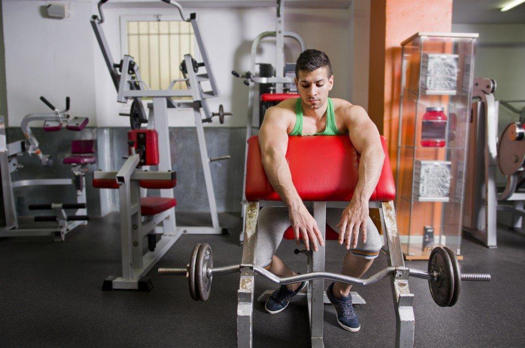 Man in gym with weights bar, biceps exercise