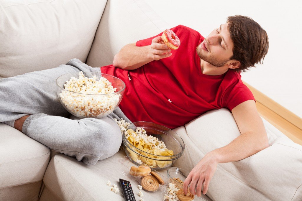 A man lying on a couch with sweets and popcorn in a mess